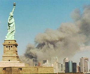 A monumental green copper statue of a woman with a torch stands on an island in front of a mainland where a massive plume of gray smoke billows amongst skyscrapers.