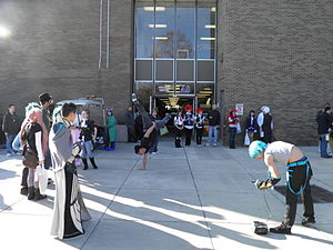 People in costumes watching someone breakdancing in front of a building