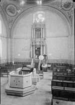 A sepia photograph shows the interior of the synagogue. In the foreground lies the reading desk atop a simply-paneled almemar. Rows of wooden benches line the right and left side of the nave. The holy ark, set in the centre of the eastern wall, is decorated with baroque carvings and set off against four Corinthian columns. Its top reaches a large clover-shaped window, which sits just below one of the four supporting arches. The walls faintly show decorative murals, with two large round frescos situated at the top left and right corners.