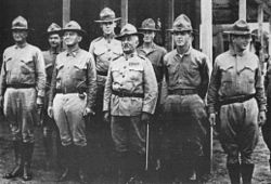 Eight people in military uniforms. They are wearing hats and are standing in formation.