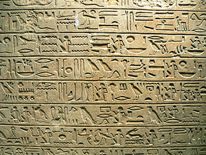 A flat stone surface, beige in color, with incised markings of Egyptian hieroglyphs written in clearly-marked horizontal columns