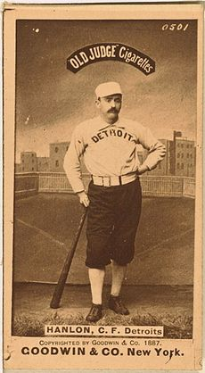 A baseball player is shown standing in his uniform, leaning on the end of a baseball bat.