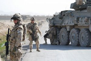 Canadian Grenadier Guards in Kandahar Province standing by road with armoured car
