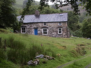 A colour photograph of a stone cottage on a hill