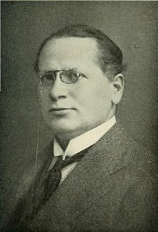 Portrait of a middle-aged man wearing glasses and a suit.