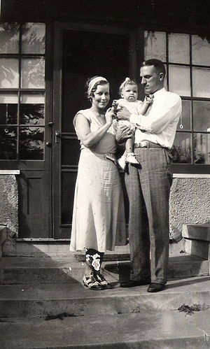 A couple stand on the front steps of a house. The man, aged about 30, dressed in grey flannels and a white shirt, holds a baby girl in his arms and gazes at her. The woman, dressed in a frock and co-respondent shoes from the 1930s stands next to them, touching the baby girl and smiling at the camera. The baby is dressed in a white frilly frock, white shoes and with a white ribbon in her hair.