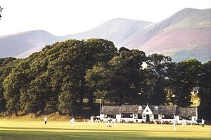 Cricket ground with wooded hills at the rear