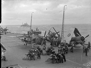 Black and white photograph of several groups of men bent over bombs on the flight deck of an aircraft carrier at sea. Several monoplane aircraft are parked on the flight deck, and another warship is visible on the sea near the carrier.