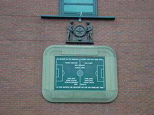 A stone tablet, inscribed with the image of a football pitch and several names. It is surrounded by a stone border in the shape of a football stadium. Above the tablet is a wooden carving of two men holding a large wreath.