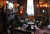 Cluttered room with fireplace, three armchairs and a violin
