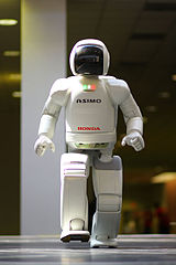 A white-bodied robot with a black face plate walks.