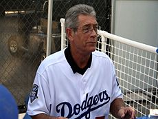 "A gray-haired white male, wearing a white uniform with ""Dodgers"" across it, sitting in a bullpen with a white fence in the background."