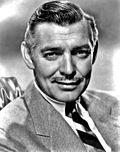 Black and white promo photo of Clark Gable in 1940—a middle-aged white man with mustache and straight gray hair combed to the side, wearing a suit and smiling.