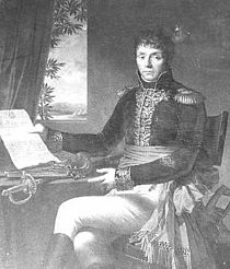 Black and white print of a man in dark military coat with gold braid and white breeches. Seated at a table, he gestures with his left hand toward a document held in his right hand.