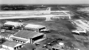 Black-and-white photo of a runway and hangars. Only one large airplane can be seen.