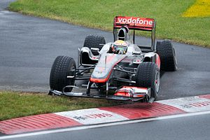 Lewis Hamilton driving a McLaren Formula One car with a damaged left rear tyre