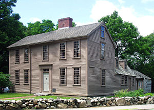The main part of the home is a wooden, two-and-a-half story rectangular building with large windows, one central door, and a central chimney. A smaller wing extends back from the right side. There are large trees in the background and a low rock wall in the foreground.