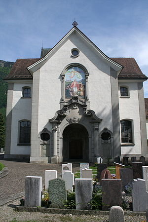 A baroque-style church, white walls with tile roof, and a set of grave stones in front of it.