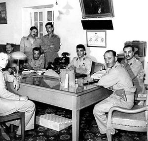 Eight men in dressed in military uniform, posing in a room around a rectangular table. All the men, except for third and fifth persons from the left are seated. The third and fifth person from the left are standing.