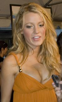 A young blonde female wearing an orange dress. The female is making a hand gesture with her right hand.