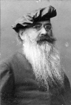 An elderly, bearded white man wearing glasses and a beret