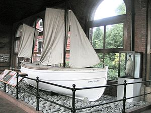 "White-hulled small boat sitting on a base of stones behind a rail, within a museum. The name ""James Caird"" is visible. A stuffed penguin in a glass case stands nearby."
