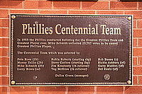 A dark bronze plaque listing the names and positions of members of the Centennial team in gold lettering