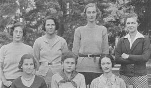 Four women stand behind three seated women, all facing the camera.