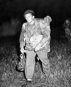 man in British Army uniform, carrying a parachute helmet and wearing a beret, other men can just be seen in the dark background
