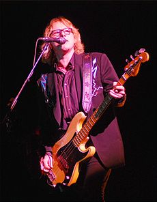Mike Mills plays bass guitar and sings into a microphone while wearing a Nudie suit