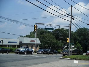 A four lane undivided road lined with businesses at a traffic light. A sign on the traffic light pole reads Old Budd Lake Road.
