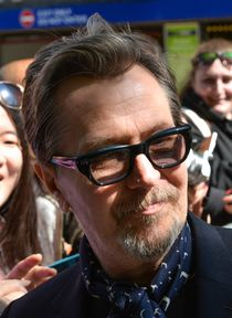 Photo of the 2018 recipient of the Best Actor award: Gary Oldman—a white male from England pictured in 2014 at 56 years of age, with brown hair brushed up and back, a salt-and-pepper goatee, wearing eyeglasses and a dark suit jacket with a white shirt.