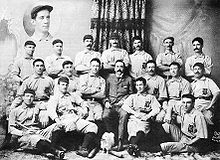 "Three rows of men in white baseball uniforms and dark caps; the rear row is standing, the middle row is seated (with a man in a tweed suit in the middle), and the front row is seated on the floor. The baseball uniforms have a dark Old English-style ""B"" over the left breast."