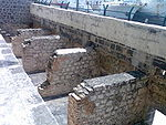 A picture of four rectangular stone structures a few feet high, laid against a wall of a larger height.