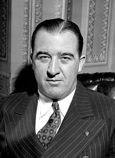 A man with dark, slicked-back hair wearing a pinstriped black jacket, patterned tie, and white shirt