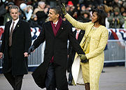Barack and Michelle Obama hold hands and smile while walking; she waves to a crowd. She wears a gold embroidered dress and coat; he wears a black overcoat and burgundy scarf. A serious man in a dark suit watches nearby.