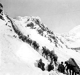 Prospectors ascending the Chilkoot Pass in a long line