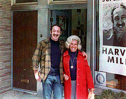 A color photograph of Milk with long hair and handlebar mustache with his arm around his sister-in-law, both smiling and standing in front of a storefront window showing a portion of a campaign poster with Milk's photo and name
