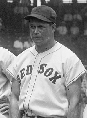 "A man is pictured from his belt up looking to the left of the camera. His button-down baseball jersey says ""RED SOX"" across it and he is wearing a baseball cap."