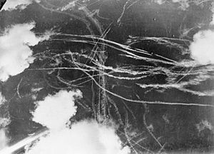 A picture of a piece of sky with several clouds and many condensation trails caused by many aircraft. Each trail curves around the other indicated an air battle
