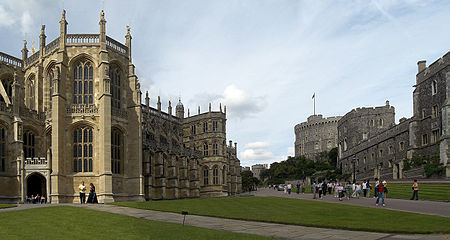 A photograph of a large Gothic chapel on the left, with tall thin windows. On the right is a line of stone buildings, pointing towards a circular tower in the middle of the picture. In the centre are two paths surrounded by grass, with a number of people walking around.