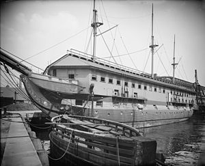 A ship tied to dock with a housing structure over top of the decks
