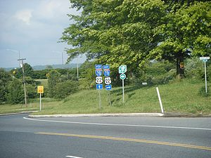 A three lane surface road at an interchange with an Interstate highway. A set of signs on the right side of the road reads west Interstate 78 U.S. Route 22 straight ahead, east Interstate 78 U.S. Route 22 right, and New Jersey Turnpike right