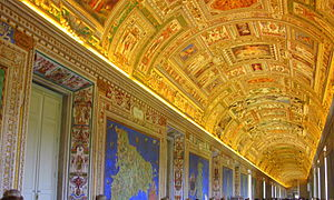 Photo of a long wide corridor filled with a crowd of people in casual dress. The ceiling is arched and is elaborately decorated with gilt stucco and small brightly coloured pictures. The walls have frescoes of large maps, each of which has a brilliant blue background.
