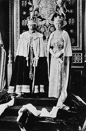 Late-middle-aged George and Mary in crowns and ermine capes stand on a dais