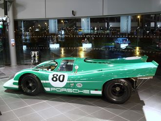 A picture of a green racing sports car from the side in an indoor setting