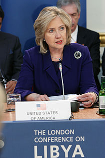 "Hillary Clinton speaks at a London meeting to discuss NATO military intervention in Libya on March 29, 2011. She is standing behind a blue podium with a sign that has the words ""THE LONDON CONFERENCE ON LIBYA"" printed in white-on-blue text in capital letters."