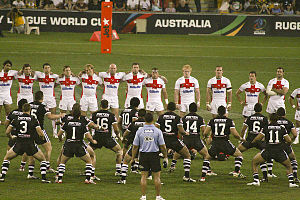Rugby team wearing all black, with backs to the camera, squatting and facing toward a team wearing white and red