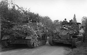Two armoured vehicles one cowered in tree branches on a hedge lined road