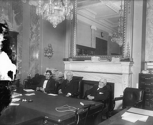 Three white men in suits sitting at a table, with a chandelier hanging and a mirror in the background